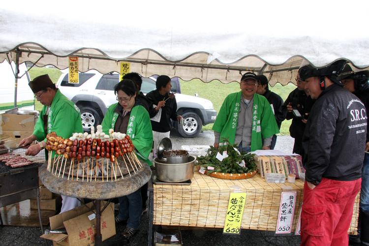 地元猪苗代町から参加した宝来堂さん(http://www.hou-raido.com/ )。笹団子、紫黒餅で視線を、焼き団子で鼻孔を、そして地元の豚を炭火で焼いた串物で霧雨の中の参加者の食欲を直撃。まさか、今日のためにハッピもカワサキ系???