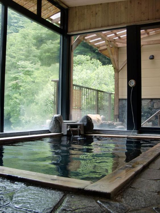 「さわんど温泉 梓湖畔の湯」の内風呂と露天風呂。眼下には上高地から雪解け水が流れ込む梓川が流れえている