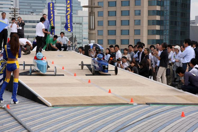 夢の大橋では緩やかな傾斜を利用し、ハンドルとブレーキだけで走る「ソープボックスダービー」が行われる。WEBサイトhttp://www.odaibagakuensai.com/の専用フォームから応募すれば体験試乗も可能だ。写真は6日(土)に行われたメーカー対抗戦の模様。