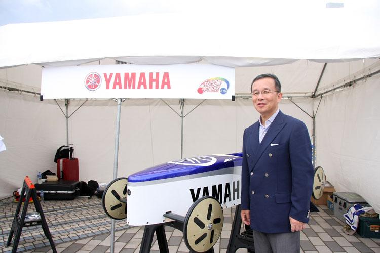 美しいファクトリーレーシング・カラーを纏ったマシンと、ヤマハF1プロジェクトリーダーとしても知られる木村隆昭代表取締役専務執行役員