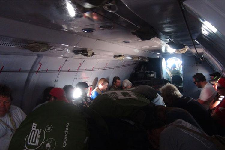 飛行機で移動するクルーもいる。その飛行機はまるで輸送機。通勤時間帯の路線バスのような混雑した様子が分かる