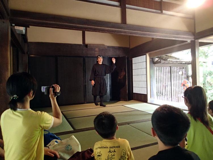 黒装束の忍者さん(?)が部屋の仕掛けを丁寧に教えてくれる。写真はよく見聞きする壁に仕掛けられた回転扉を解説しているところ