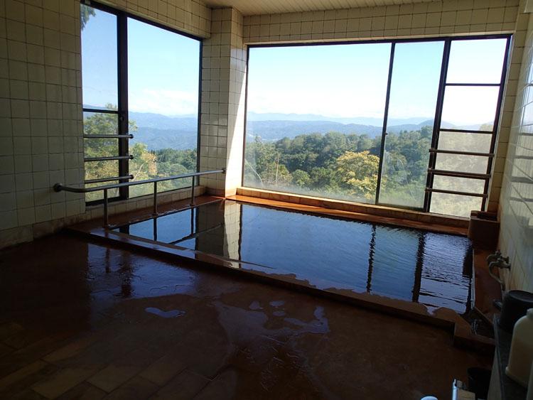 山間に佇む関温泉にある旅館「登美屋」の浴室からの眺めは絶景。熱めのお湯は茶褐色の濁り湯で、良質な温泉であること漂わせている