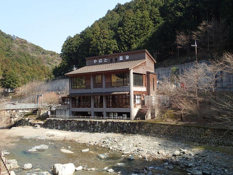 四郷川沿いに建てられている「やはた温泉」。内風呂は四郷川に面しており、周囲の景色が眺められる。四郷川の透明度はバツグン