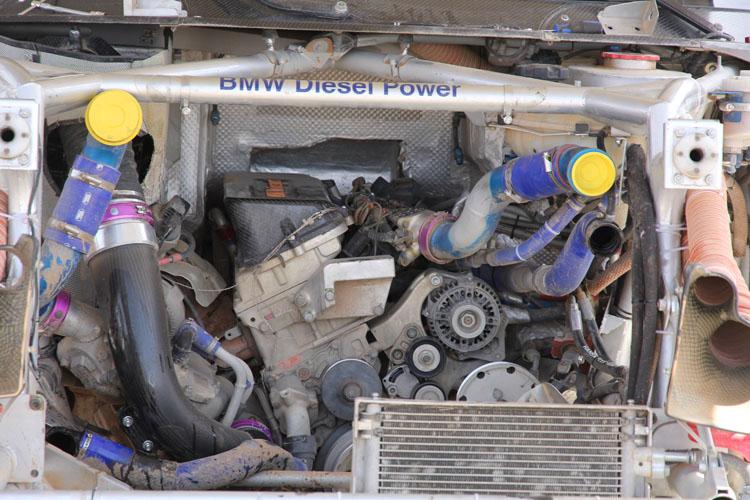 アイドリングからまるでジェットエンジンのような音を奏でるそれは、バルクヘッドに食い込むようにマシンセンターに近い位置に積まれている。まるでアルミ削り出しのようなエンジン外観(ということはマツダのように圧縮比はそれほどたかくないのだろうか……)。どう見てもレーシングエンジンにしか見えない。ディーゼルらしいカラカラ音も皆無。ラリーでのライバル、トヨタ・ハイラックスが積むレクサス用V8が高回転域の刺激的な音を奏でるのにたいし、こちらはターボF1みたいに音が静かに聞こえた。ナッサーはロビー・ゴードンのチームで2駆のハイパワーバギーを走らせた経験もあるが、ラリーに必要なのはディーゼルパワーと4駆だと断言する。2015年、プジョーも2008DKRというマシンでダカールに復帰するが、あの車も2駆。ナッサーの言葉通りだとすれば、プジョーをドライブするカルロス・サインツ、シリル・デュプレ、ステファン・ペテランセルという優勝経験豊富な彼らがどのように闘うのか楽しみだ