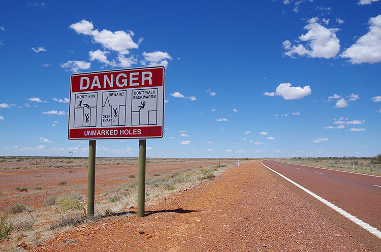 クーバーペディの名物看板。オパール採掘のための穴に落ちないよう注意!の意味。