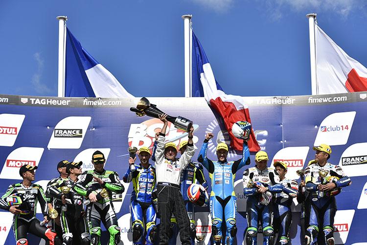 真ん中で巨大なトロフィーを掲げるSERTのドミニク監督、誰よりも強い存在感を放つ、そして、誰よりも声援を集めるスター、日本人ライダーの北川圭一は、ここで世界チャンピオンライダーになりました