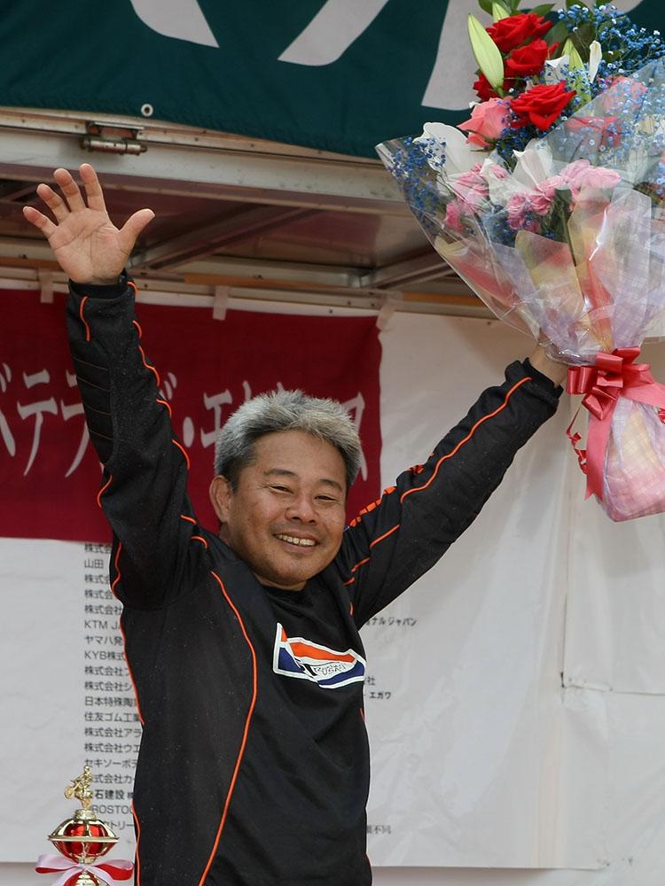 ジャパンVET恒例のレジェンド表彰は、90年代にスズキファクトリーで活躍した松田強氏が受賞。40代最後となるVET+40クラスを激走し、ステージトークでは現役時代の思い出などを披露した。ジャパンスーパークロスで5万人の観衆がツヨシコールの大ウェーブに湧いた話は日本MX界の伝説。当時の現場を知るてっぺーさんが聞き手だけに深イイ話が連発。現在の松田氏は故郷の沖縄でNPO法人『こども安全運転振興会』理事長、MXコース『イマナゴクロスフィールド』オーナーとして活躍する