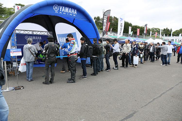 ヤマハモーターサイクルの頂点に君臨するYZR-M1の現車に跨がれるとあって、開場早々に列に並んで順番を待つ参加者達は順番が来ると最高の笑顔で自分のカメラに納まっていた