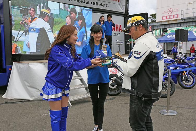 壮絶な競り合いで勝ち取ったお宝の商品を、参加者達は満面の笑みでレースクイーンから受け取っていた