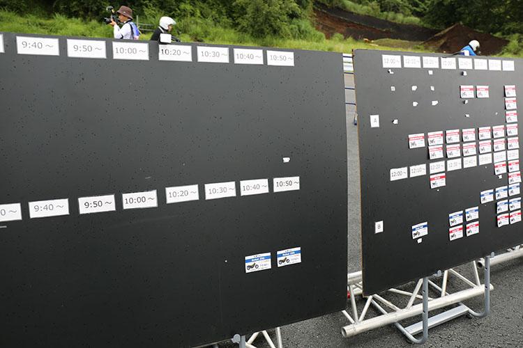 試乗会場の試乗カードが貼られたボード前で乗りたいマシンのカードを探すオーナー達